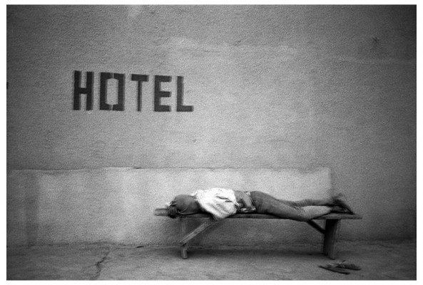 man sleeping on a bench in front of a hotel